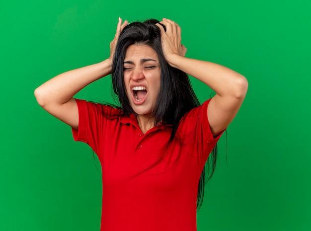 緑の壁に隔離された頭痛に苦しんで目を閉じて頭に手を置く痛む若い病気の女性