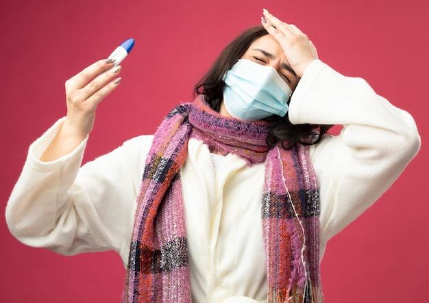 분홍색 벽에 고립 된 닫힌 눈으로 머리에 손을 넣어 온도계를 들고 마스크와 가운과 스카프를 착용하는 아픈 젊은 아픈 여자
