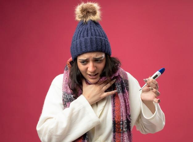 Giovane donna malata dolorante che indossa il cappello invernale della veste e la sciarpa che tiene il termometro che esamina il lato che mette la mano sulla gola isolata sulla parete rosa