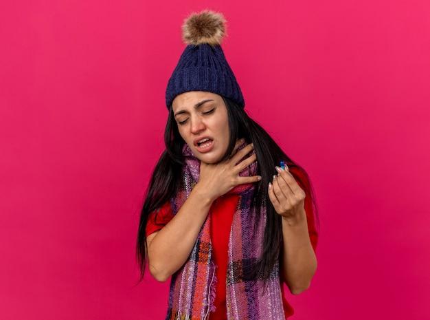 Giovane donna malata dolorante che indossa cappello invernale e sciarpa che tiene la capsula e la sua gola con gli occhi chiusi isolati sulla parete rosa