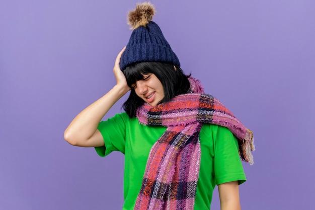 Giovane donna malata dolorante che indossa cappello invernale e sciarpa tenendo la mano sulla testa con mal di testa con gli occhi chiusi isolato sulla parete viola con spazio di copia