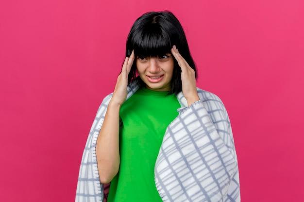 Dolorante giovane donna malata avvolta in un plaid tenendo le mani sulla testa guardando dritto isolato sulla parete rosa con spazio di copia