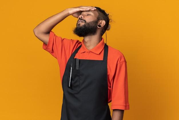 복사 공간이 있는 주황색 벽에 격리된 닫힌 눈으로 머리에 손을 얹고 제복을 입은 젊은 남성 이발사