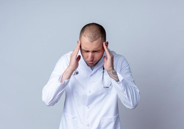 Giovane medico maschio dolorante che indossa veste medica e stetoscopio intorno al collo mettendo le mani sulle tempie che soffrono di mal di testa con gli occhi chiusi isolati su bianco con spazio di copia