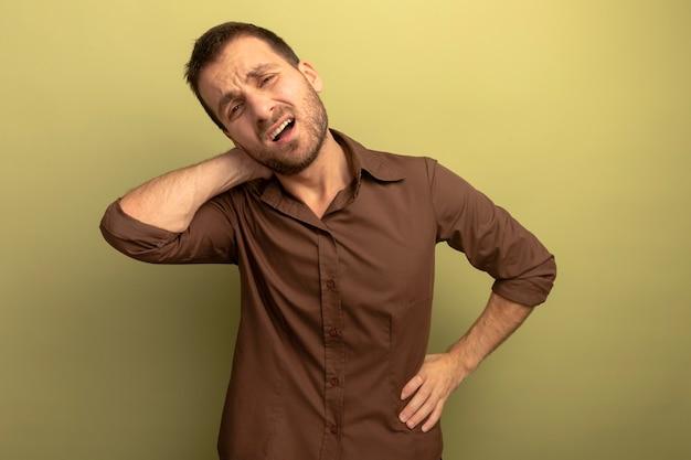 オリーブグリーンの壁で隔離の正面を見て腰と首に手を置く痛む若い男