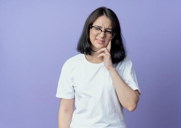 Dolorante giovane bella ragazza caucasica con gli occhiali mettendo le dita sulla guancia guardando il lato che soffre di mal di denti isolato su sfondo viola con spazio di copia