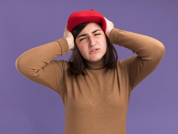 頭を保持しているベレー帽の帽子を持つ若いかなり白人の女の子を痛める