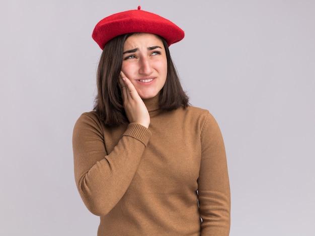 ベレー帽の帽子をかぶった痛む若いかなり白人の女の子は顔に手を置き、白で横を見る