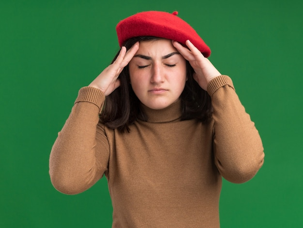ベレー帽の帽子で痛む若いかなり白人の女の子は緑の額に手を置きます