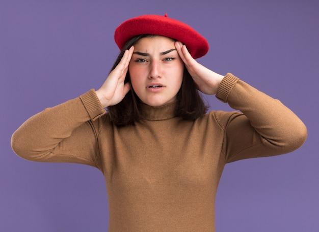 ベレー帽の帽子で痛む若いかなり白人の女の子は頭に手を置きます