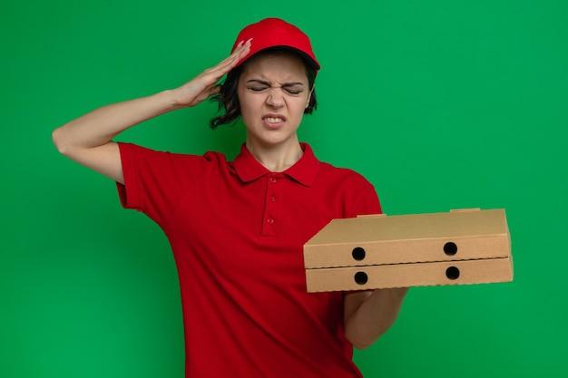 Giovane e graziosa donna delle consegne dolorante che tiene in mano scatole per pizza e si mette la mano sulla testa
