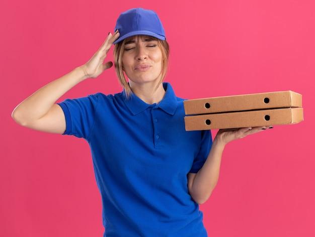 Dolorante giovane donna graziosa di consegna in uniforme mette la mano sulla testa e tiene le scatole per pizza isolate sulla parete rosa