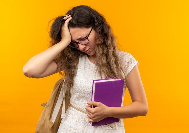 Giovane studentessa graziosa dolorante con gli occhiali e borsa posteriore che tiene il libro mettendo la mano sulla testa guardando verso il basso isolato su giallo con spazio di copia