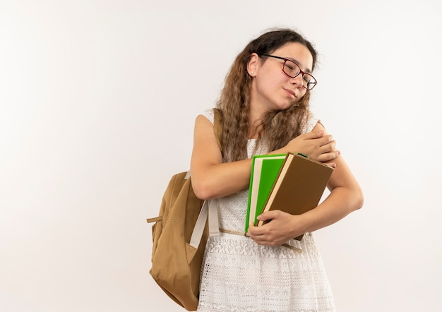 Giovane studentessa graziosa dolorante con gli occhiali e borsa posteriore che tiene i libri mettendo la mano sul braccio con gli occhi chiusi isolati su bianco con lo spazio della copia