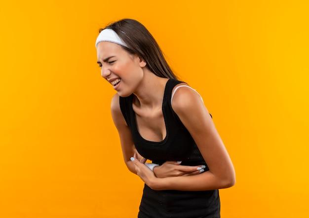 Болит молодая симпатичная спортивная девушка с повязкой на голову и браслетом, держащая живот, страдающая от боли с закрытыми глазами, изолированная на оранжевой стене
