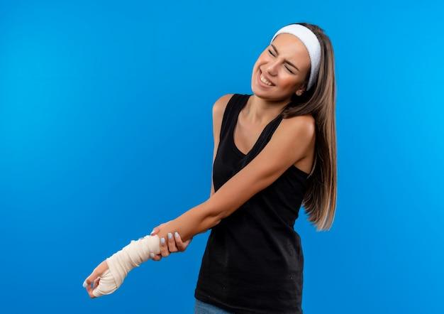 Болит молодая симпатичная спортивная девушка с повязкой на голову и браслетом, держащая травмированное запястье, перевязанное повязкой, с закрытыми глазами, изолированными на синей стене