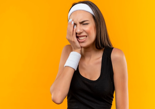 Болит молодая симпатичная спортивная девушка с ободком и браслетом, положив руку на лицо с закрытыми глазами, изолированными на оранжевой стене с копией пространства