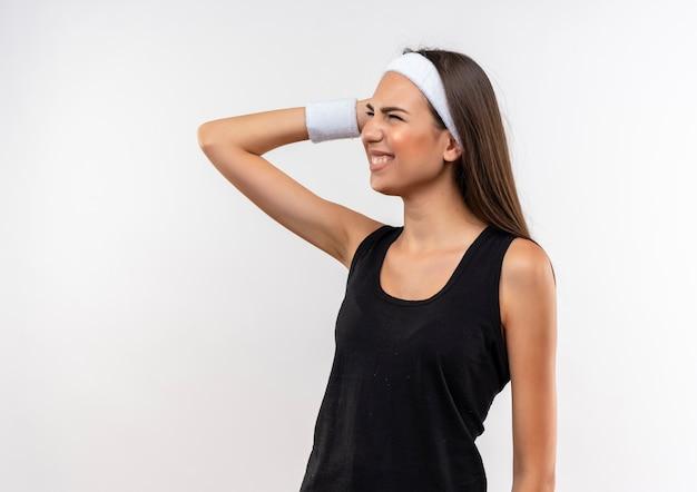 Болит молодая симпатичная спортивная девушка с повязкой на голову и браслетом, положив руку на голову, глядя в сторону на белой стене с копией пространства