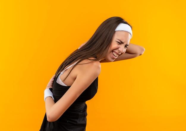 Болит молодая симпатичная спортивная девушка с ободком и браслетом, положив руки на спину, стоя в профиль, изолированном на оранжевой стене