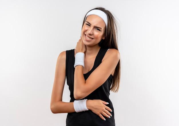 Болит молодая симпатичная спортивная девушка с ободком и браслетом, положив руки на шею и живот на белой стене