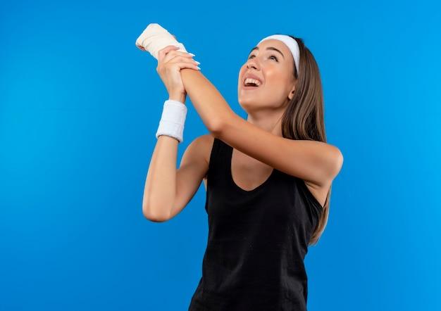 Болит молодая симпатичная спортивная девушка с повязкой на голову и браслетом, поднимающая и держащая травмированное запястье, перевязанное повязкой, и глядя вверх изолированно на синей стене