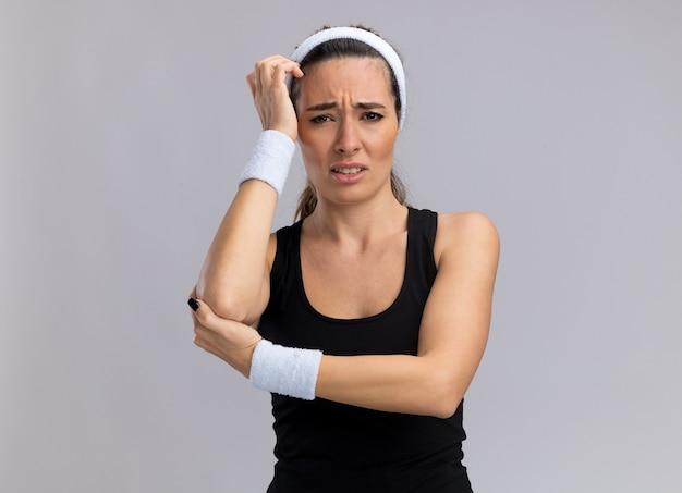 머리띠와 팔꿈치에 손을 유지하는 팔찌를 착용하는 아픈 젊은 꽤 스포티 한 소녀