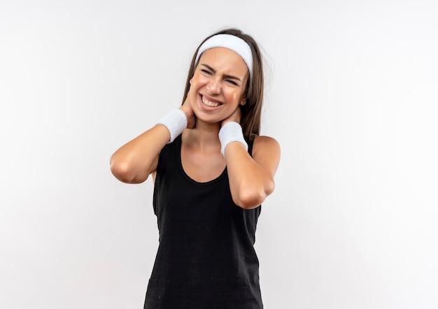 Giovane ragazza abbastanza sportiva dolorante che indossa fascia e cinturino che si mette le mani sul collo sul muro bianco