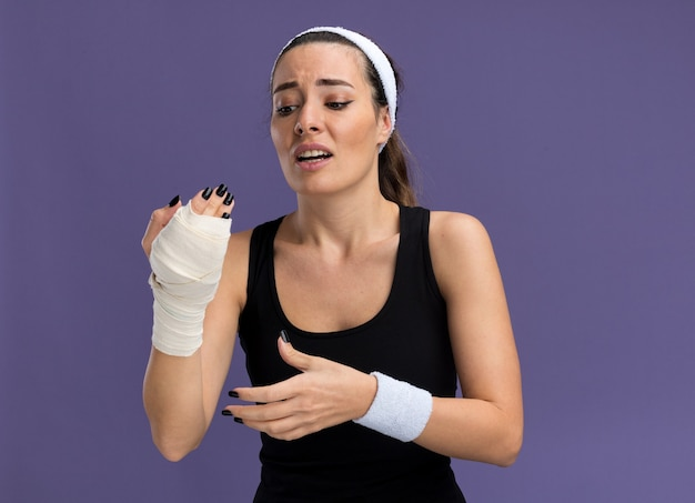 Aching young pretty sporty girl wearing headband and wristbands looking at injured wrist wrapped with bandage keeping hands in air isolated on purple wall with copy space