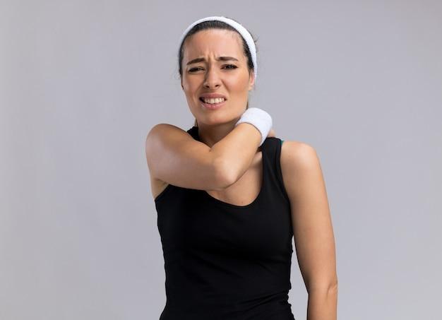 Болит молодая симпатичная спортивная женщина с повязкой на голову и браслетами, положив руку на спину