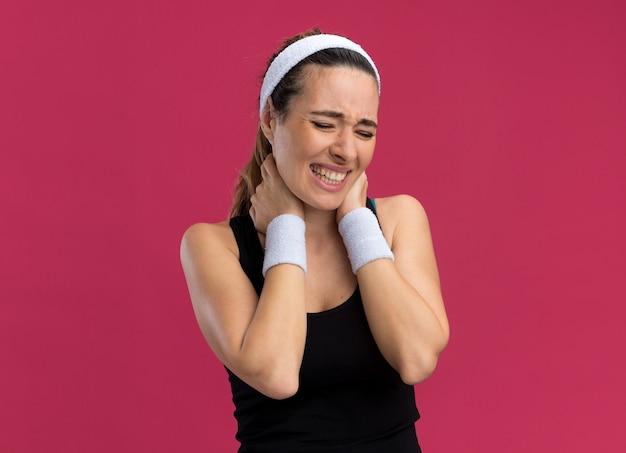 Giovane donna abbastanza sportiva dolorante che indossa fascia e braccialetti che tengono le mani sul collo con gli occhi chiusi