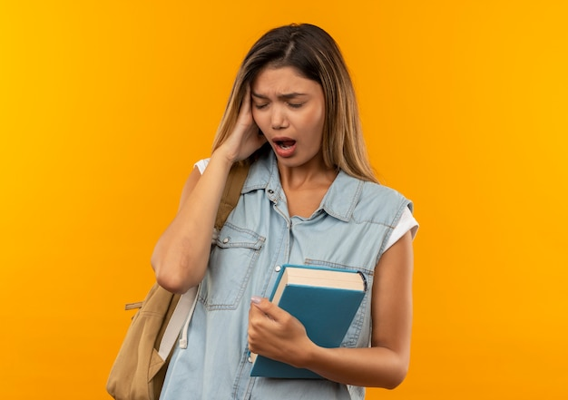Ragazza giovane e graziosa studentessa dolorante che indossa la borsa posteriore che tiene libro mettendo la mano sulla testa che soffre di mal di testa con gli occhi chiusi