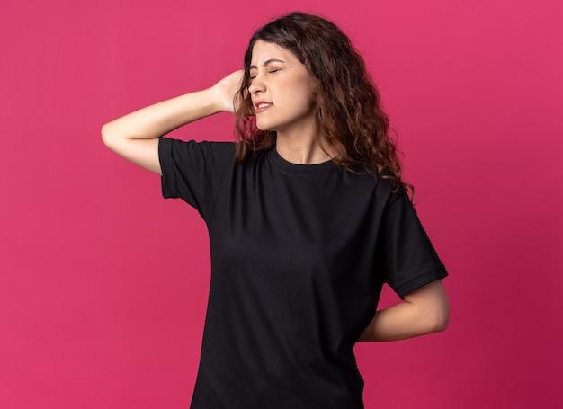 진홍색 벽에 격리된 닫힌 눈으로 머리와 등에 손을 대고 있는 아픈 젊은 예쁜 여자