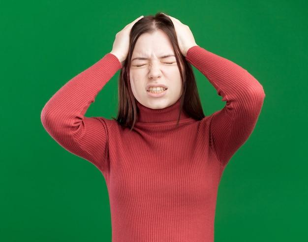 Giovane bella donna dolorante che tiene le mani sulla testa con gli occhi chiusi isolati sul muro verde