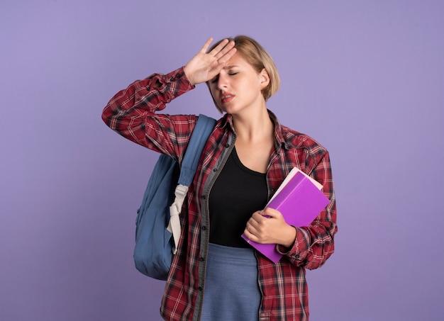 Una giovane studentessa slava dolorante che indossa uno zaino mette la mano sulla fronte tiene un libro e un taccuino