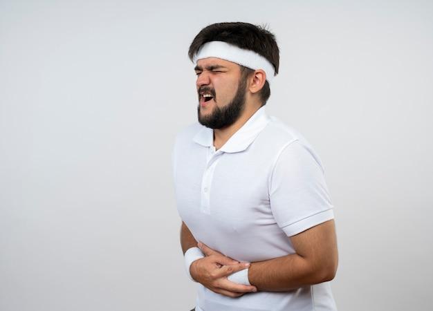 閉じた身に着けているヘッドバンドとリストバンドを持つ痛む若いスポーティな男は、コピースペースで白い壁に分離された痛む胃をつかみました