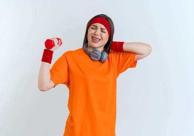 首にヘッドバンドとリストバンドとヘッドフォンを身に着けている痛む若いスポーティな女性は、目を閉じて隔離された首の後ろに手を置くダンベルを保持しています