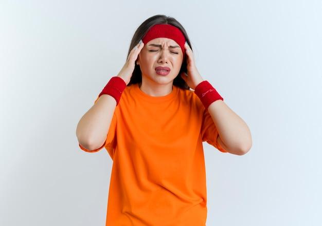 복사 공간이 흰 벽에 고립 된 닫힌 눈으로 두통으로 고통 머리를 들고 머리띠와 팔찌를 착용하는 젊은 스포티 한 여자를 아프게
