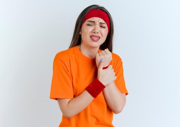 복사 공간 흰 벽에 고립 된 닫힌 눈으로 손목을 잡고 머리띠와 팔찌를 착용하는 젊은 스포티 한 여자를 아프게