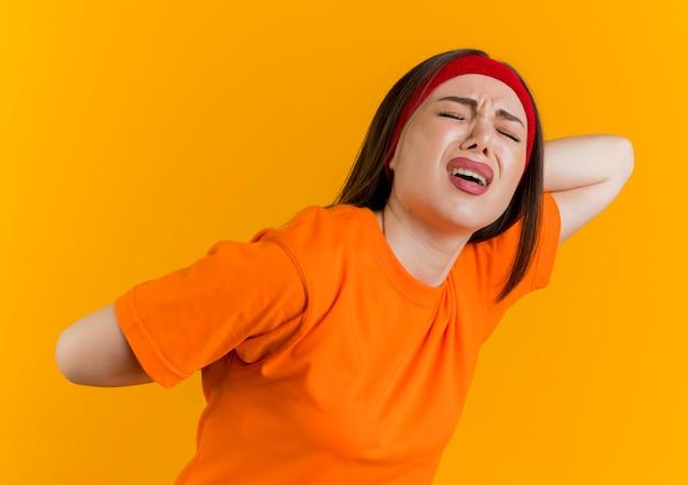 목 뒤와 뒤에서 손을 유지하는 머리띠와 팔찌를 착용하는 젊은 스포티 한 여자가 아프다.