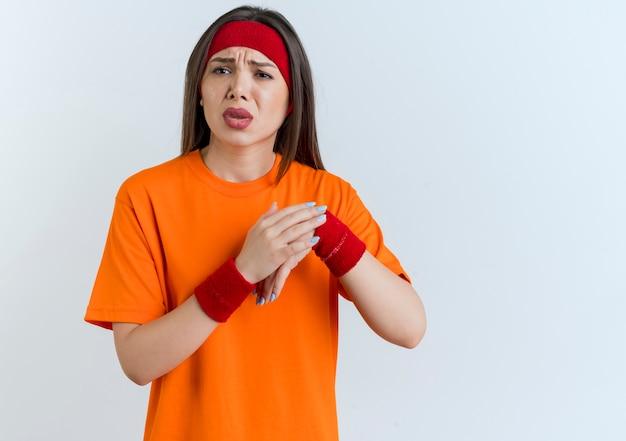 복사 공간이 흰 벽에 고립 된 다른 하나에 손을 넣어 측면을보고 머리띠와 팔찌를 착용하는 젊은 스포티 한 여자를 아프게