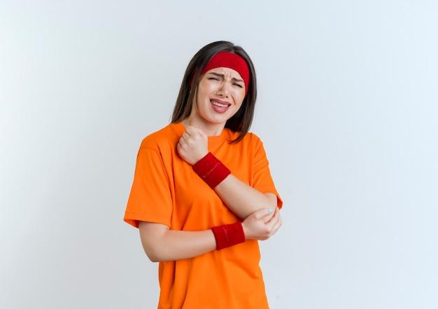 孤立した肘に手を置くヘッドバンドとリストバンドを身に着けている痛む若いスポーティな女性