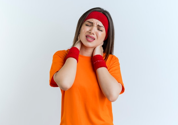 복사 공간이 흰 벽에 고립 된 닫힌 눈으로 목에 손을 댔을 머리띠와 팔찌를 착용하는 젊은 스포티 한 여자가 아프다
