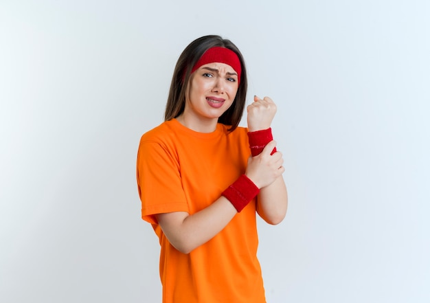 Aching young sporty woman wearing headband and wristbands clenching fist looking holding wrist isolated