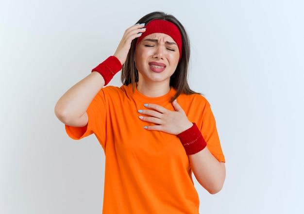 Dolorante giovane donna sportiva che indossa fascia e braccialetti tenendo le mani sulla testa e sul petto con gli occhi chiusi