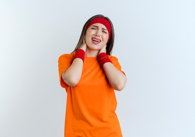 Aching young sporty woman wearing headband and wristbands looking holding neck isolated