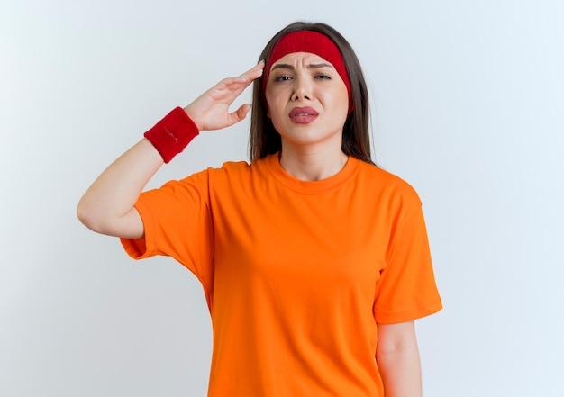 Dolorante giovane donna sportiva che indossa la fascia e braccialetti alla ricerca di toccare la testa