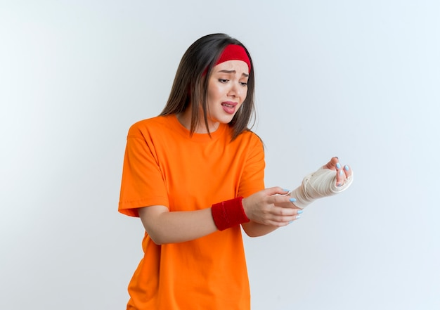 Aching young sporty woman wearing headband and wristbands touching and looking at injured wrist wrapped in bandage isolated