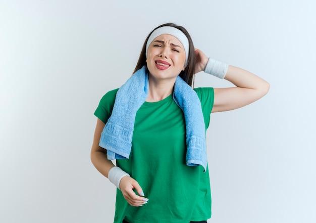 Dolorante giovane donna sportiva che indossa la fascia e braccialetti con asciugamano intorno al collo cercando di tenere la mano dietro la testa