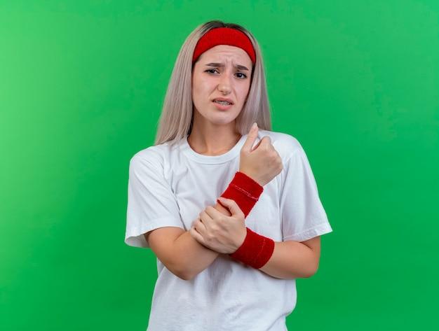 La giovane donna sportiva dolorante con le parentesi graffe che indossa la fascia e i braccialetti tiene la mano isolata sulla parete verde