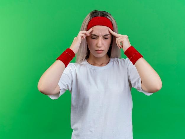 Dolorante giovane donna sportiva con bretelle che indossano fascia e braccialetti mette le dita sulle tempie isolate sulla parete verde
